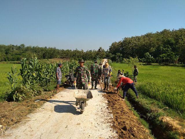 Warga dan Satgas TMMD sedang melaksanakan pembereman jalan
