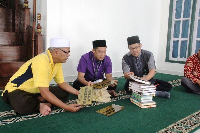 Ibnu Isnaini bersama Fajri saat membagikan kebutuhan masjid.