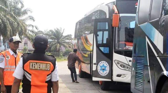 Petugas memeriksa bus yang masuk