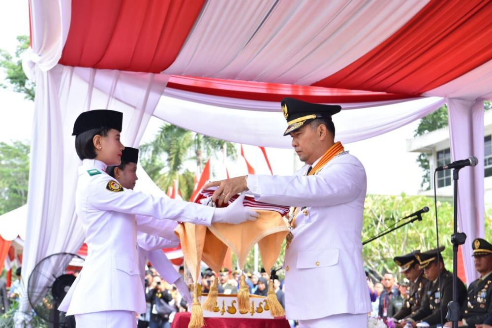 Fasha menyerahkan bendera
