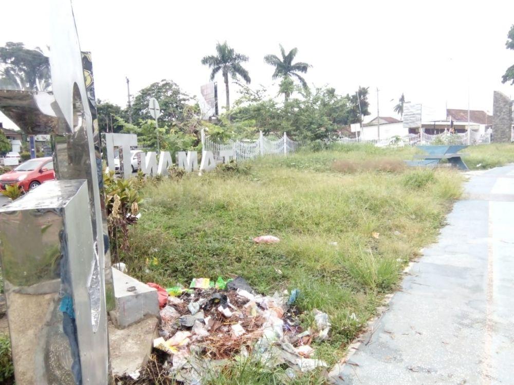 Sampah berserakan dengan rumput yang tinggi