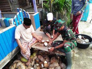 Bagai Satu Keluarga, Anggota Satgas Ini Ikut Bantu Kupas Kelapa Warga