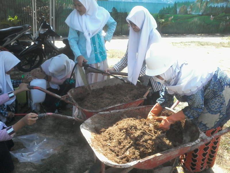 Siswa sedang melakukan proses pencampuran bahan utama tandan kosong kelapa sawit (TKKS) dengan sekam padi, kotoran ayam dan pasir bangunan serta pelembaban dengan penambahan Ectiviti Mikroorganisme (EM4)