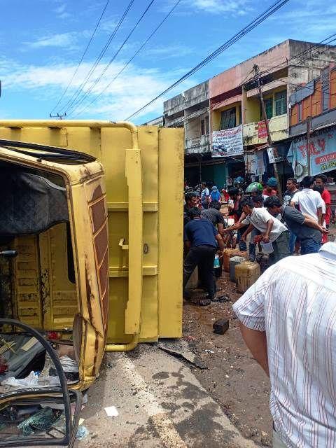 Truk terbalik membawa tangki yang diduga berisi minyak mentah dikerumuni warga